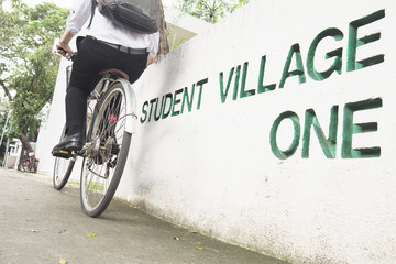 Student is riding bicycle in village green campus