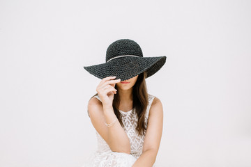 Young pretty woman in white dress with black hat near white wall.