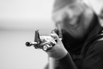 tactical police in tactical gear aim rifle in black and white color