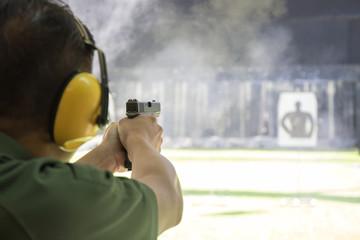 man shooting automatic  pistol to target in shooting range Wall mural