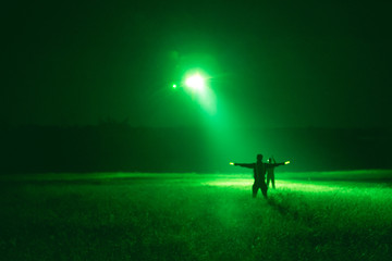 marshaller signal to helicopter for night landing from night vision goggles view