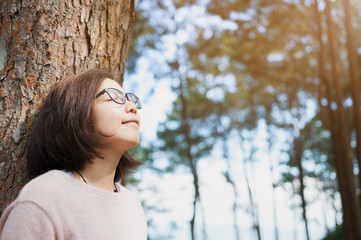 Woman smiling and breathing fresh air at pine forest with sunlig