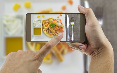 People using mobile phone taking photo of colorful waffles on white plate