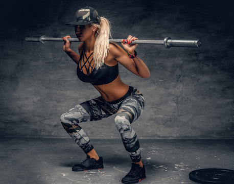 A woman doing squats with a barbell.
