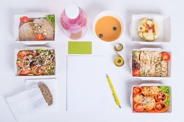 План здорового питания на день для одного человека. Блюда в крафт коробках, блокнот, ручка, визитка, сантиметровая лента и деток-вода на белом фоне.