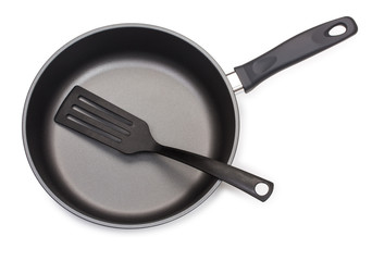 Black frying pan with cooking utensils: plastic paddle, isolated