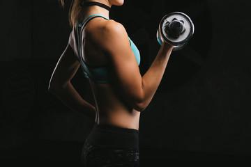 Sport fitness woman training on dark background. Beautiful body