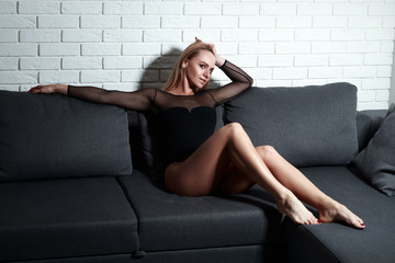 sexy slim girl in the bodysuit, blonde on couch