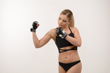 Young beautiful blonde sexy boxing girl posing with gloves on wh