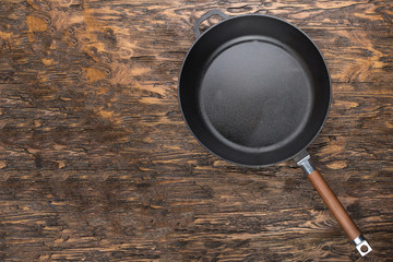 a cast-iron frying pan on a wooden background