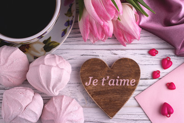 Valentine's day elegant still life with tulip flowers cup of coffe marshmallows zephyr red heart shape sign on white wooden background and lettering I Love You in French