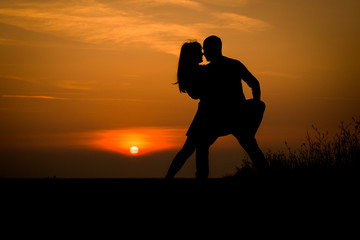 silhouette teenager lovers couple with sun between on sunset dusk sky background: black shadow hand drawn of people hug and kiss people:passion in love concept:decoration,design,valentines