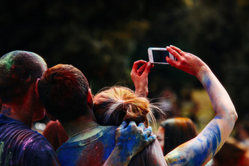 happy people taking selfie photo on mobile at holi fest, festiva