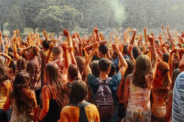 hands and happy people crowd partying under rain at holi fest, f