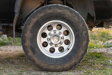 SUV car wheel on dirty rural road