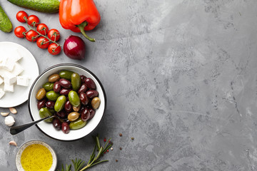 Greek salad ingredients: fresh olives, feta cheese, tomatoes, pepper, cucumbers, onion, rosemary and olive oil on stone background
