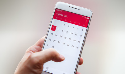 Hand with a smartphone with a calendar, one month plans