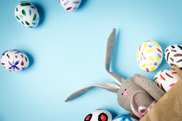 Easter bunny in a paper bag. Blue background. Easter ideas. Easter eggs. Space for text.