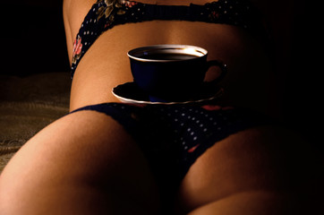 Dark blue cup of tea in a saucer on the sexy body of slim beautiful girl, who resting on the beige bed. The concept of privacy at a tea party with girlfriend. Erotic background