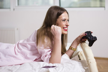 Happy young woman playing a video game. Beautiful woman relaxing at home. Fun time playing with a remote joystick. Relaxing on a Sunday evening.