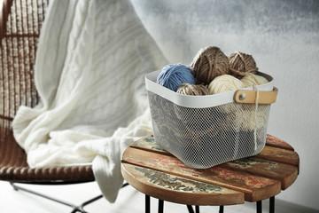 Plastic box with knitting yarn on stool