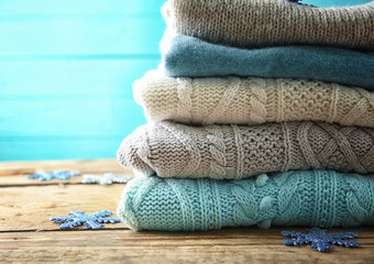 Stack of woolen clothes on wooden background, closeup