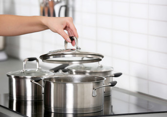 Woman cooking on modern stove at kitchen