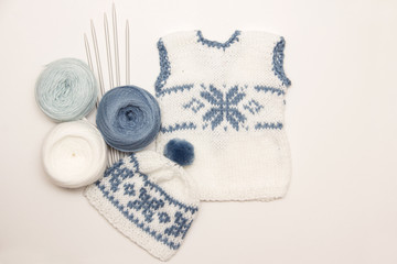 knitting clothes for the newborn on a white background. needles