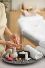 Woman holding wooden balls in spa salon, closeup