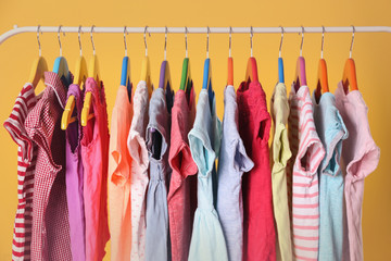 Hangers with different clothes on yellow background