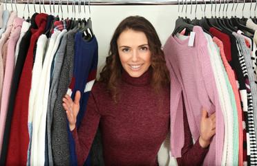 Beautiful young woman choosing clothes in modern shop