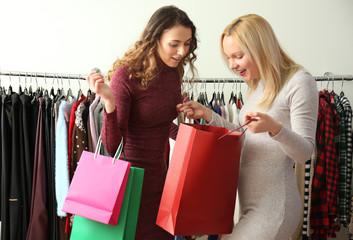 Beautiful young women buying clothes in modern shop