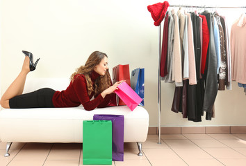Beautiful young woman with paper bags lying on couch in modern shop