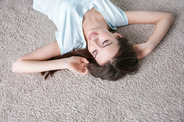 Happy young woman lying on soft floor in light room