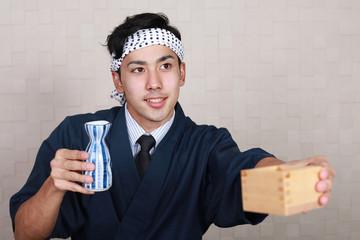 お銚子を持つ笑顔の寿司職人