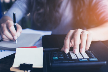 Businesswoman use the calculator to calculate and analyze the co