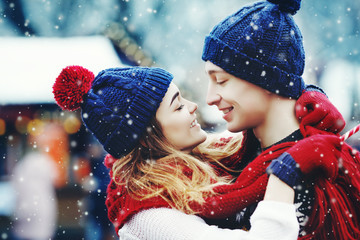 Outdoor close up portrait of young beautiful happy smiling couple posing on street.  Models hugging, looking at each other, bundled up in red scarf, wearing stylish blue hats. Snowfall. City lifestyle