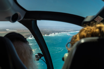 """Helicopter Flight at 12 Apostles. Helicopter flight at famous """"12 Apostles"""", Great Ocean Road, Australia. Taken from the inside, two women sitting in the front of the cockpit."""