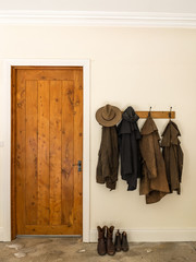 Historic Australian Farm Clothes in South Australia, near Robe. Leather jackets, boots and a hat. Clothes hanging next to a rustic wooden door.