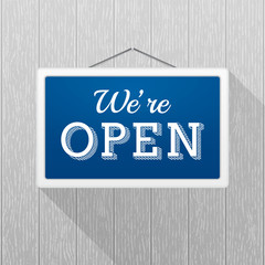 Simple blue sign with text 'we're open' hanging on a gray wooden wall. Wood texture with vertical stripes, rustic panels