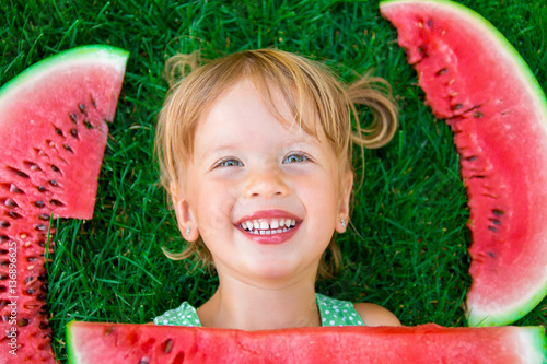 5ef2a635f952 Happy little blonde girl lying on the grass with big slice watermelon in  summer time. Smiling. Top view.