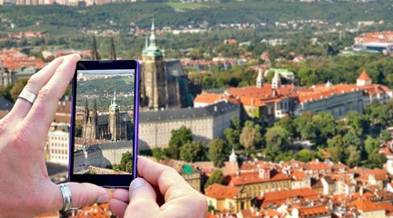 View over the mobile phone display during shooting Prague Castle in Prague. Holding the mobile phone in hands and taking a photo, focused on mobile phone screen.