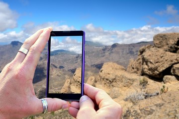 View over the mobile phone display during shooting Gran Canaria mountains. Holding the mobile phone in hands and taking a photo, focused on mobile phone screen.