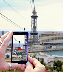 View over the mobile phone display during shooting cable car in Barcelona. Holding the mobile phone in hands and taking a photo, focused on mobile phone screen.