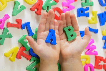 Little girl learning to read using magnetic letters holding in hands a and b. Learn Study Education School Knowledge Concept