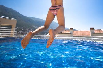 Slim woman in bikini jumping in swimming pool on the roof