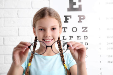 Little girl with spectacles on ophthalmic test chart background
