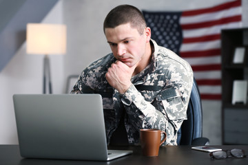 Soldier working with laptop in headquarters building