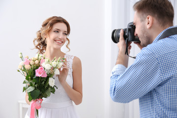 Wedding photographer taking photo of beautiful bride in studio