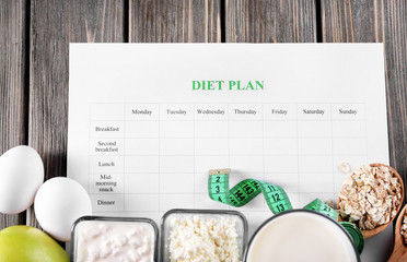 Different products, diet plan and measuring tape on wooden background